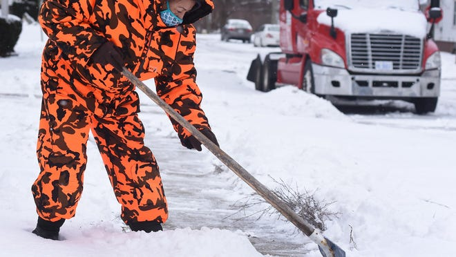 "Charlene Martinez of Monroe, who moved to Monroe from Georgia last year, shovels snow Friday morning on Island St. in the City of Monroe. ""I just love the snow,"" said Martinez who purchased her bright orange snow outfit at a yard sale for $10. ""I love Monroe, the people are so nice."""