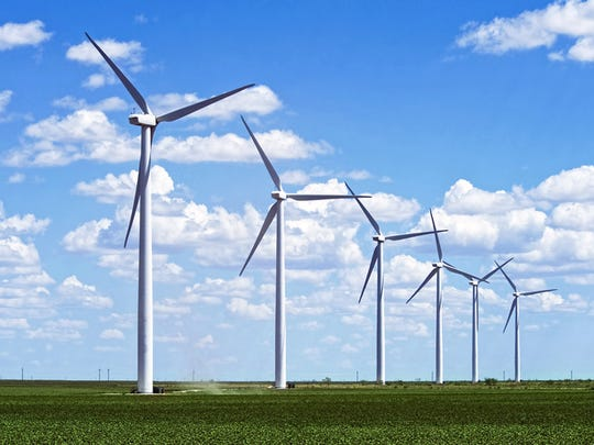 A row of wind turbines in a field.
