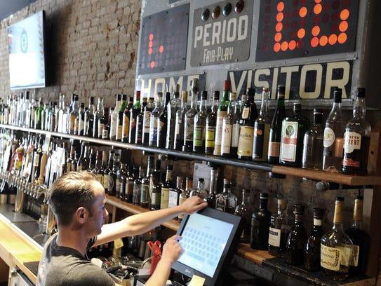 Bartender Andrew Wainio, 41, of Detroit, runs patrons'