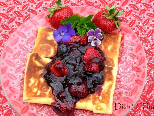 Cheese blintzes are topped with a sweet berry topping.