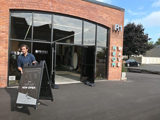 Owner Fred Rainaldi puts out the Now Open sign at the