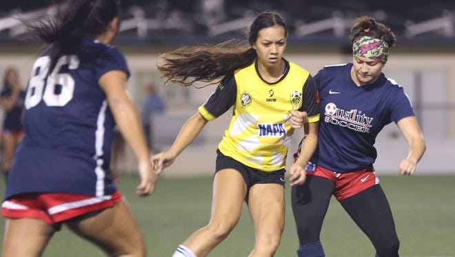 NAPA Lady Rovers' Brianne Leon Guerrero (in yellow) tries to keep the ball away from Quality Distributors' Breanna Lai during a Week 4 match of the Bud Light Women's Soccer League Premier Division Sunday at the Guam Football Association National Training Center. The Lady Rovers won 1-0.
