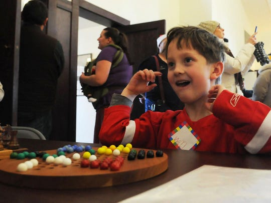 "Will Brandon of Lebanon, Wis., celebrates after a game of Chinese checkers in his Christmas sweater at last year's ""Christmas in the Village"" in Ephraim. It was among the old-fashioned games offered at Village Hall by the Ephraim Historical Foundation."