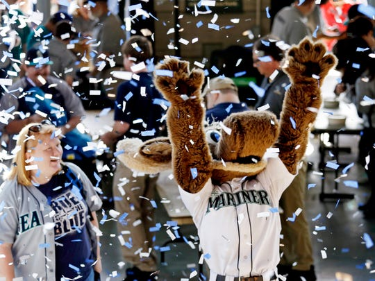 The Seattle Mariners' mascot, the Mariner Moose, raises his arms amid a cloud of confetti as the ballpark's gates open before the baseball team's home-opener against the Oakland Athletics, Friday, April 8, 2016, in Seattle.