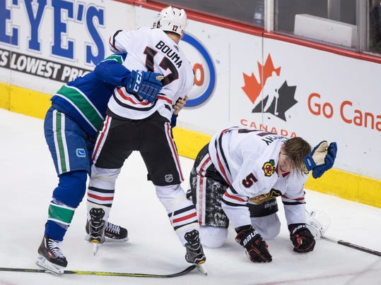 Chicago Blackhawks' Lance Bouma (17) and Vancouver Canucks' Alex Biega, left, fight after Chicago's Connor Murphy, right, was checked into the boards during the second period of an NHL hockey game Thursday, Dec. 28, 2017, in Vancouver, British Columbia. (Darryl Dyck/The Canadian Press via AP)