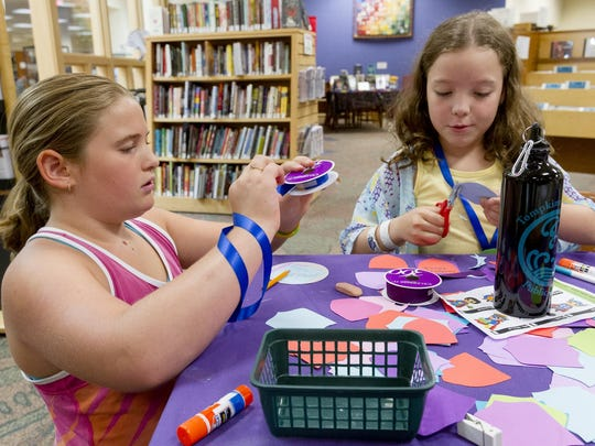Hatteras Greenspun, 10, left, and Gabby Mccain, 9, make superhero badges Wednesday morning at the conclusion of the Tompkins County Public Library's summer reading program. In the background is the current teen space.