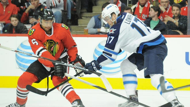 Chicago Blackhawks defenseman Trevor Daley (6) and Winnipeg Jets left wing Adam Lowry (17) battle for the puck during the second period at United Center.
