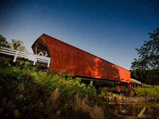 Stars shine over the Roseman covered bridge built in Madison County 1883 is photographed in this long exposure around 2 A.M. Wednesday, Aug. 26, 2015.