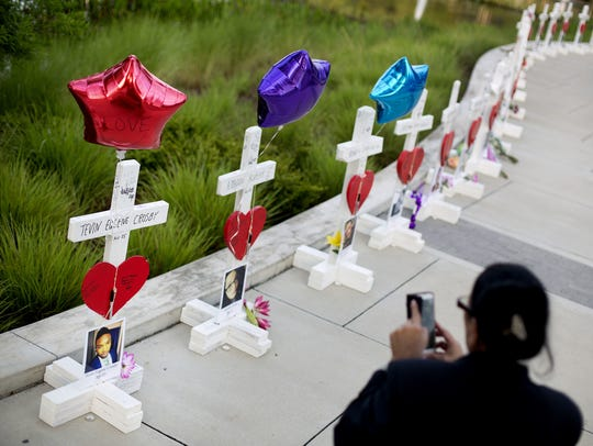 Crosses, one for each victim, line a walkway Friday