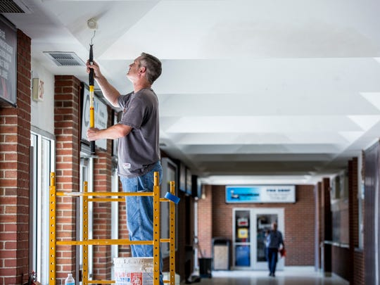 Contractor Brian Armstead works on painting a hallway on the south side of McMorran Place Wednesday, August 10, 2016 in downtown Port Huron.
