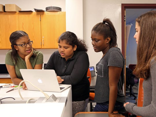 Student technicians Leila Miller, 15, left, Harsha Philip, 14, and Athena Clark, 15, help Lauren Rogers, 14, connect to the wi-fi at Briarcliff Manor High School.