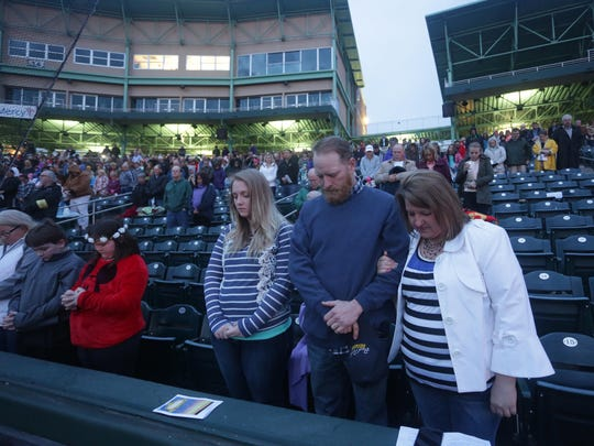 A family prays at the start of the Easter Sunrise Celebration at Hammons Field.
