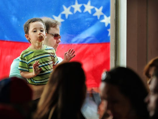 Two-year-old Valentino Giorgi looks for his mom as she lines up at the Casa D'Leon event venue in East Memphis to vote alongside hundreds of fellow Venezuelan nationals in an unofficial referendum designed to put pressure on President Nicolas Maduro over unpopular constitutional reforms.