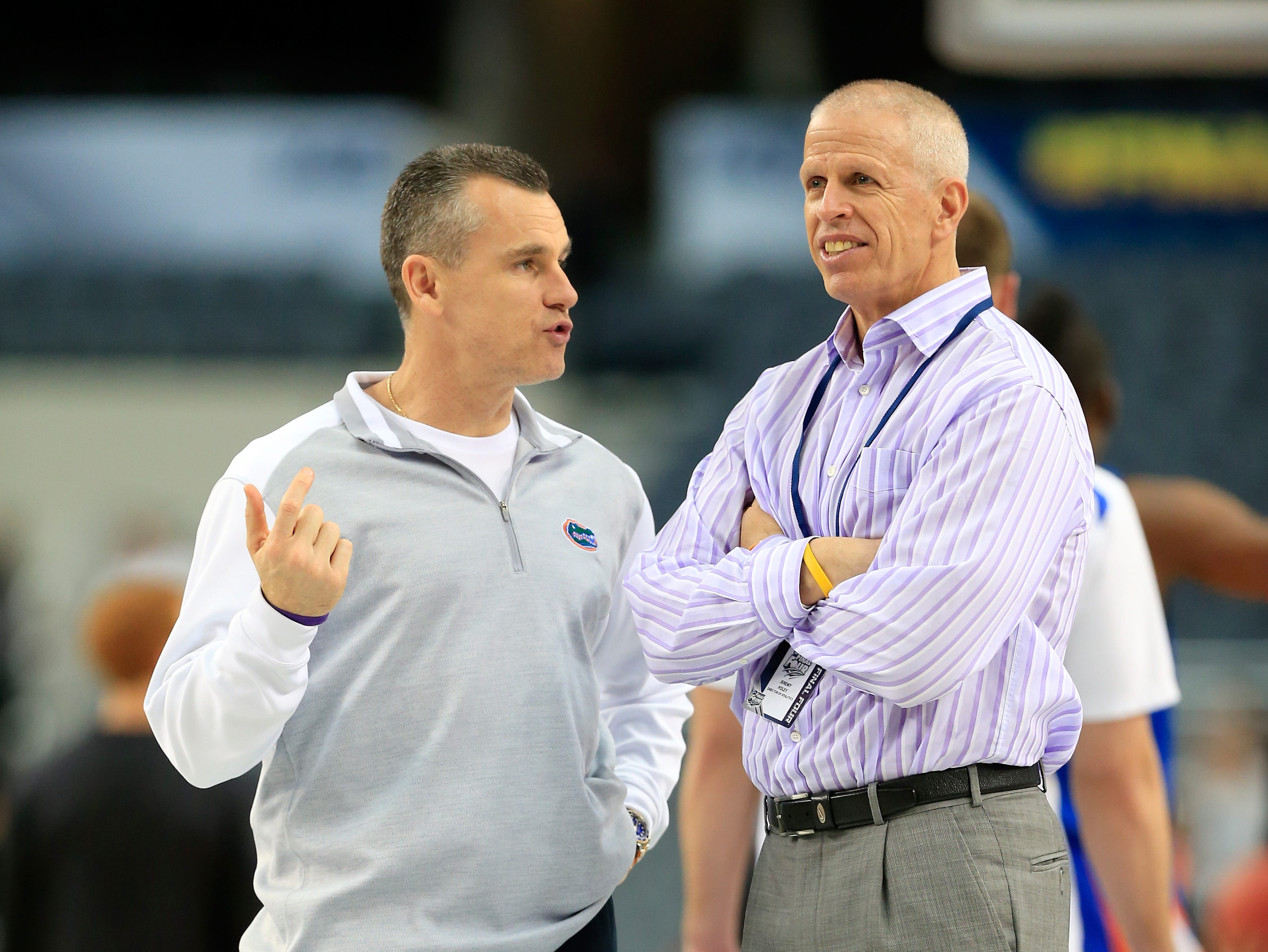 Head coach Billy Donovan of the Florida Gators talks with athletic director Jeremy Foley.