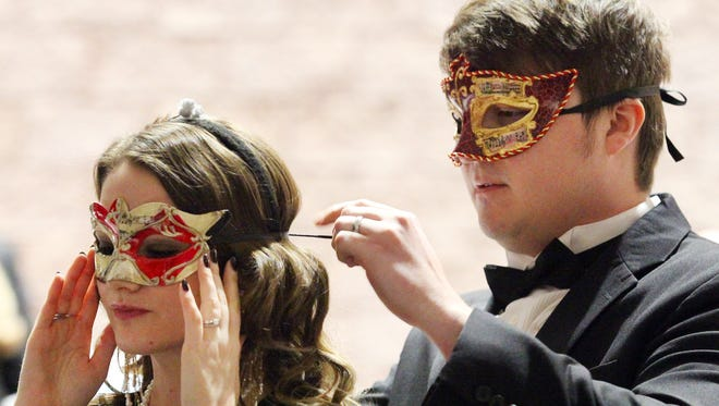 Connor Ayers helps Erica Ayers tie on a mask at a previous Cotton Ball at the Civic Center of Anderson.