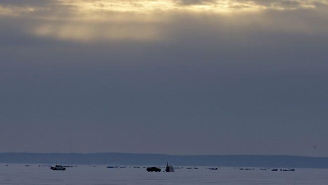 Sunlight breaks through clouds Saturday as the 2017 sturgeon spearing season gets underway on Lake Winnebago near Waverly Beach in Menasha.
