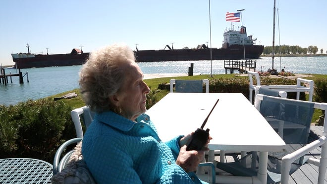 From her back deck, Arlene Earl talks to the passing freighter, the Maple Glen, after it saluted her with a blast of its horn. Earl, who is known as the Flower Lady, has been giving flowers to captains of freighters for over 20 years as a thank-you to them. A former florist in southwest Detroit, she sends the bouquets to the freighters via the J.W. Westcott mail boat.