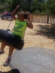 Dericka Lindsay plays on a tire swing. Authorities