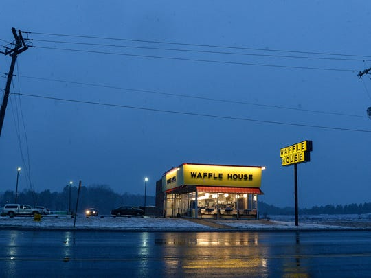 The sky gets lighter in the early morning while customers get away from snow for food at the Waffle House in Pendleton on Wednesday, January 17, 2018.