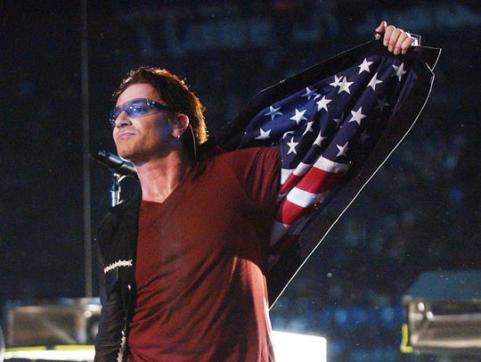 Bono, lead singer of U2, displays American flag lining