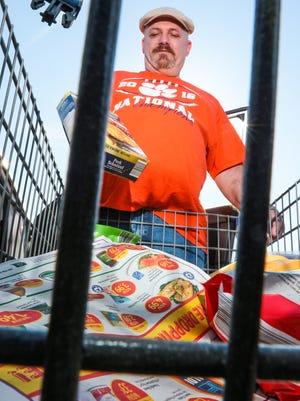 Bill Rector of Pendleton takes groceries out of a shopping cart at his car, after shopping at the Aldi grocery store in Anderson on Wednesday. Rector said he looks forward to seeing the new store open on S.C. 28 Bypass in May.