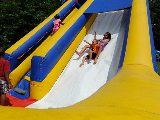 Families play on an inflatable slide during the Millbrook Police Department Cops and Kids Day in Millbrook, Ala. on Saturday June 14, 2014.