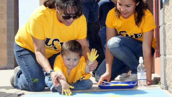 Little Angel gets help hand painting from his grandmother Carmen and Lady Cat Arianna Reyes during the 2015 World Down Syndrome Day celebration.