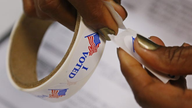 """Sue Ogrocki/AP A controversial study suggests that noncitizens living in the United States could be swinging tight elections. A poll worker rips """"I Voted"""" stickers from a roll at a polling place in Oklahoma City, Tuesday, June 24, 2014. With both of Oklahoma's U.S. Senate seats on the ballot for the first time in recent history, incumbent Jim Inhofe is seeking to fend off challengers in the Republican primary for one of the seats while two of the party's ascending stars battle for the other. (AP Photo/Sue Ogrocki)"""