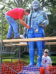 Dennis Drake (left) and Nathan Beasley start the task of pealing off the hundreds of layers of paint on the famed statue of Benjamin Franklin located at center campus of Franklin College in Franklin, Indiana. Drake is with Drake Construction and specializes in concrete work thinks this may be the frst time the legendary statue has been properly cleared of paint since it has been on campus for over 60 years.  Throughout the years students in the wee hours of the night secretly paint or decorate the staue to reflect a certain cause the student body may be celebrating.