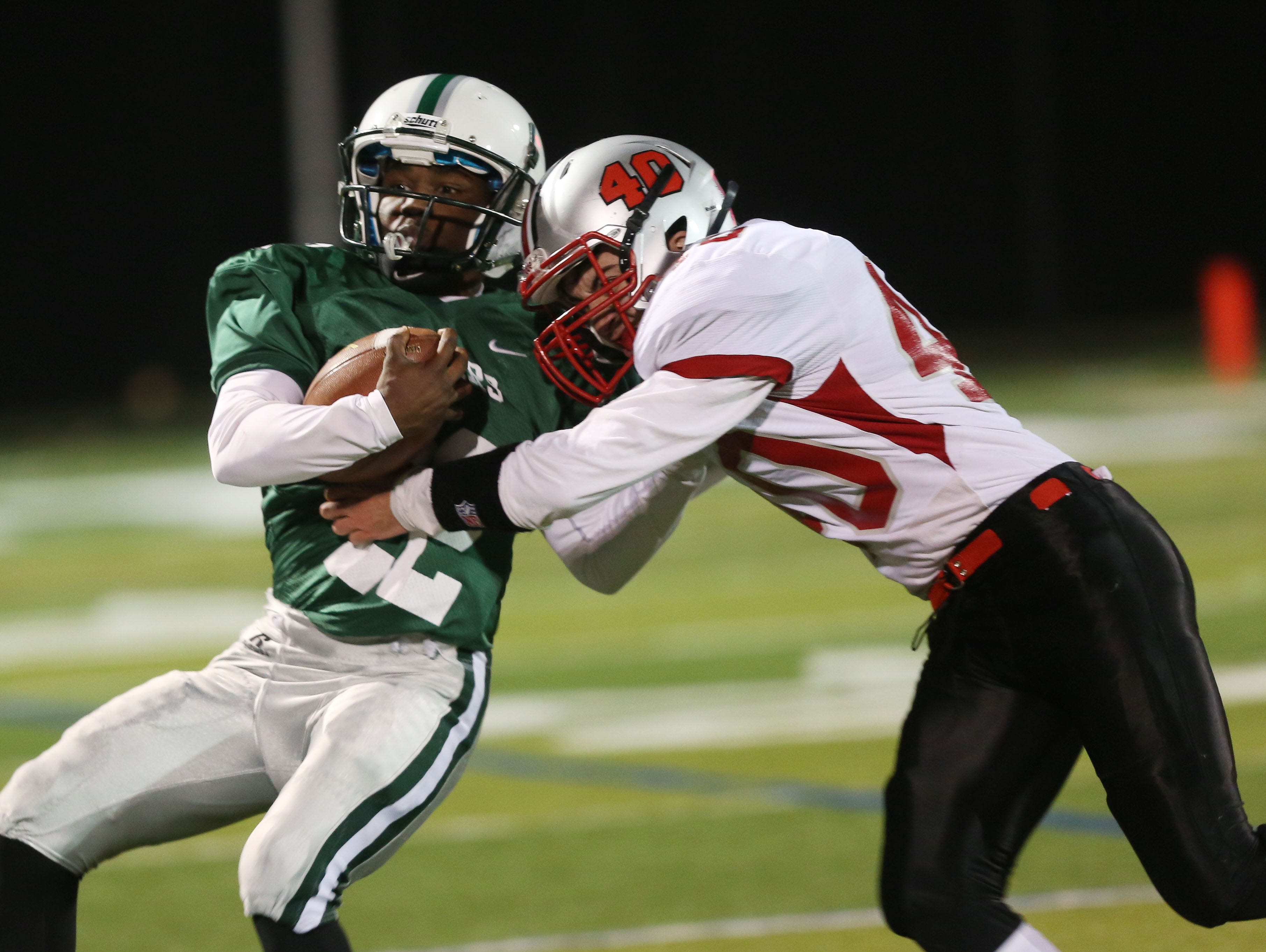 Brewster's Henry Terry tries to get away from Somers Andrew Cassin (40) on first half run during the Section 1 Class A semifinals at Brewster High School Oct. 28, 2016.