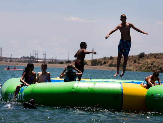 A group of swimmers play on an inflatable structure,