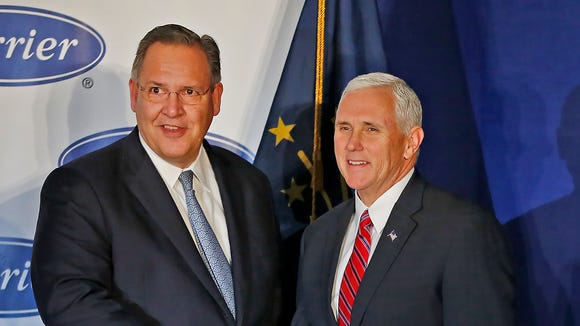 Carrier's Greg Hayes, left, shakes hands with Vice President-elect Mike Pence during an event at the Indianapolis factory, Thursday, Dec. 1, 2016, announcing that jobs would stay at Carrier and in the US. President-elect Donald Trump also spoke.