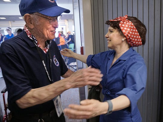 Boarding the airplane, Jim Berbrich gets a hug from Ellen Engle, dressed as Rosie the Riveter. Engle lives in Potomac, Md., but has roots in Livonia.