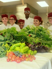 Students pose for a photo with a delivery of produce.