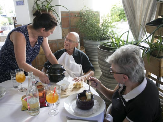 Ségolène Gros serves a dish to patrons, Richard and