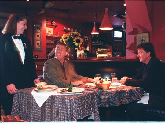 Server Linda Henderson brings lunch to Pete Sugar, left, and Gary Kendra, in November 2001 at the original Caucus Club.