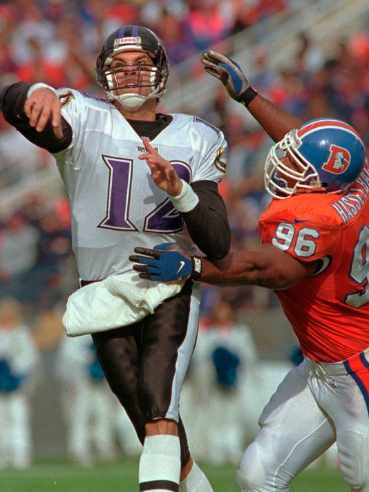 FILE - In this Oct. 20, 1996, file photo, Denver Broncos defensive end Harold Hasselbach, right, pressures Baltimore Ravens quarterback Vinny Testaverde during an NFL football game in Denver. Hasselbach's son Terran is a hybrid linebacker at Colorado. The younger Hasselbach broke his foot, ribs and a disc in his back during an accident in 2010 that happened just before he started high school. It took him three years to play again, with his father training and counseling him every step of the way. (AP Photo/Joe Mahoney, File)