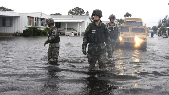 FILE - National Guard members evacuate Lamplighter Village during flooding from Tropical Storm Fay in 2008