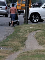 A woman pushes a baby carriage along the shoulder of