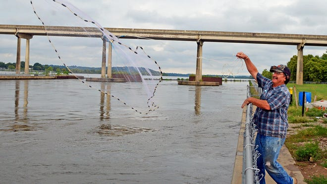 Larry Hilbern casts his net into the Arkansas River attempting to add baitfish to his bucket on Thursday, August 13, 2020. Hilbern was fishing near the Clyde T. Ellis Hydroelectric Generating Station on the Van Buren side of Trimble Lock & Dam.