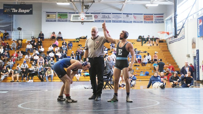 Enka senior Michael Cantrell, right, has won his 100th career match this season for the Jets.