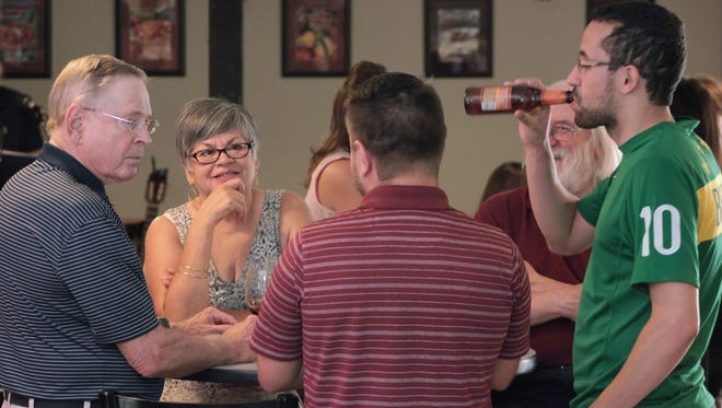 Richard Van Frank, left, and his wife, Sue Van Frank, chat with new friends during The Adjustment Project, a monthly Friday afternoon social hour hosted by the New Mexico State University School of Hotel, Restaurant and Tourism Management. Proceeds from sales of beer, wine and cocktails at TAP, as the event at 100 West Cafe in Gerald Thomas Hall is known, benefit HRTM's student clubs.
