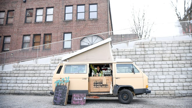 Jennifer Pauer arranges things inside of her '85 Westfalia Volkswagen bus which now the food truck Nuwati Coffee while waiting for customers at the new 69 Haywood Food Truck Court downtown on a the chilly afternoon of Wednesday, Jan. 3, 2018.