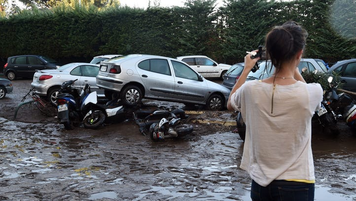 A woman takes pictures of damaged cars and motorbikes