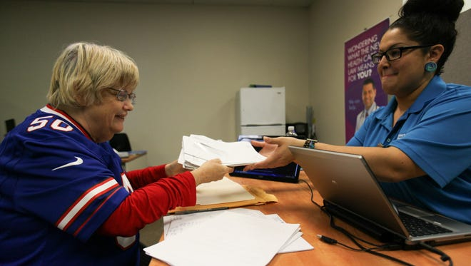 Denise Drushler hands a stack of health insurance papers to enrollment specialist Linda Domenech at Westside Health Care in Bear Thursday.