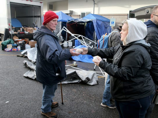 Regular Bob Poe is handed a breakfast sandwich from Pashia Braunesreither, the executive assistant from the West Sound Treatment Center, outside the downtown Bremerton Salvation Army on Thursday. The Salvation Army Building is closed due to a bed bugs outbreak.