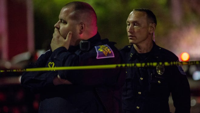 An Indiana State Police officer and an IMPD officer watch as family of the fatal shooting victim begin to arrive at Fox Hill Manor.