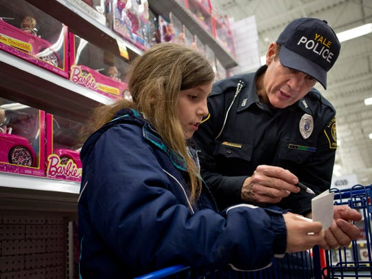 Faith Walainis, 10, of Capac, checks her list with Yale Police Officer John Borkovich during Shop with a Cop Tuesday, Dec. 15, 2015 at Meijer in Fort Gratiot.