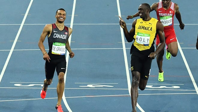 Jamaica's Usain Bolt , right, shares a laugh with Canada's Andre De Grasse after winning his 200 semifinal.