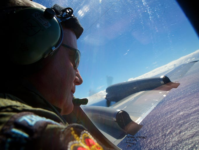 Royal New Zealand Air Force Sgt. Trent Wyatt searches for the missing Malaysia Airlines Boeing 777 from a P-3 Orion aircraft on April 11 over the southern Indian Ocean. The airliner with 239 people on board disappeared on March 8.